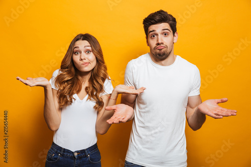Leinwanddruck Bild Image of happy young people man and woman in basic clothing throwing up arms with puzzlement, isolated over yellow background