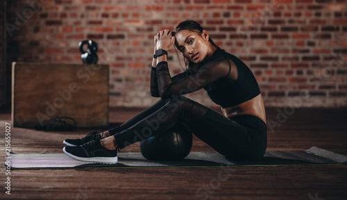 Woman resting after cross training at gym
