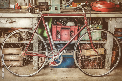 Foto Spatwand Fiets Vintage racing bycicle in front of an old work bench with tools