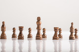 King chess piece with chess figures standing on white table