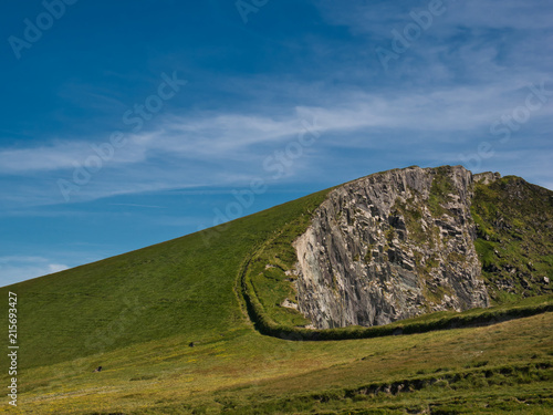 Leinwanddruck Bild Grüne Wiese direkt an einer langen runden Felskante an der Westküste von Irland