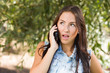 Unhappy Mixed Race Young Female Talking on Cell Phone Outside