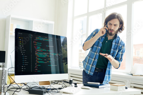 Puzzled handsome hipster young IT specialist in casual outfit asking question to customer on phone while elaborating web program for him in home office - 215707863
