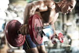Athletic man training biceps at the gym - 215708213