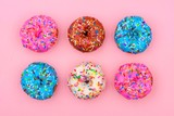 Six assorted donuts with pastel colored icing and sprinkles against a soft pink background. Minimal concept.