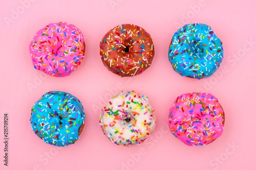 Foto Murales Six assorted donuts with pastel colored icing and sprinkles against a soft pink background. Minimal concept.