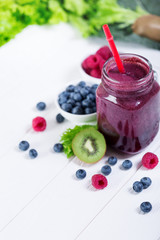 Smoothie berry bottle on white wooden board