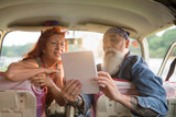 An old hipster couple sitting in a van, using a digital tablet