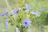 bouquet with flowers of chicory blue purple flowers and white wildflowers in a glass of water drops on the window.