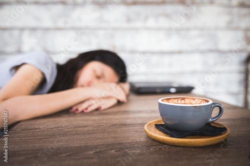 sleeping woman behind coffee drink