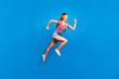 Leinwanddruck Bild - Full-size portrait of running marathon girl who looks in front of her isolated on bright blue background
