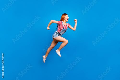 Leinwanddruck Bild Full-size portrait of running marathon girl who looks in front of her isolated on bright blue background