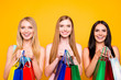 Leinwandbild Motiv Boutique center mall showroom package commerce black friday concept. Portrait of charming pretty trio holding many colorful bags in hands enjoying seasonal sales isolated on vivid yellow background