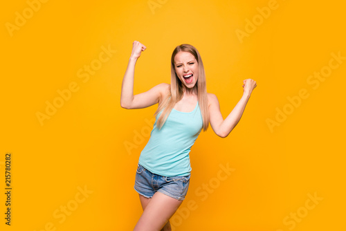 Leinwandbild Motiv Yes, they did it! Happy blond girl raises her hands in fist isolated on vivid yellow background with copy space for text