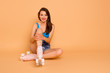 Leinwanddruck Bild - Full-size portrait of creehful and cute sweet girl sits on the floor in roller skates and hugging her knees looking at camera isolated on pastel peach background with copy space for text