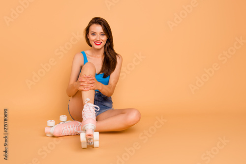 Leinwanddruck Bild Full-size portrait of creehful and cute sweet girl sits on the floor in roller skates and hugging her knees looking at camera isolated on pastel peach background with copy space for text