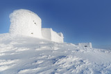 Fantastic winter landscape, snowstorm background. Observatory covered with snow in mountains.