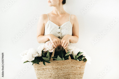 Leinwandbild Motiv Young pretty woman holding straw bag with white peony flowers on white background. Summer concept.