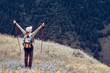 Happy Hiker with Backpack and trekking sticks looking green forest of the mountain range
