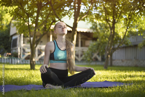 Fototapeta Young woman in the garden sitting on a yoga mat. Summer morning.