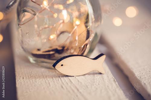 Kleiner Anker aus Holz vor Glasgefäß