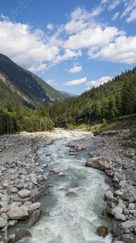 Foto Spatwand Bergrivier Flowing river in the valley with trees, rocks, moutanis