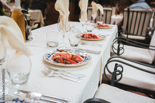 Table set up in a luxury restaurant. Salad with tomatoes, mozzarella and pepper. - 215815256