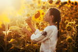 Cute child in a blossoming sunflower field