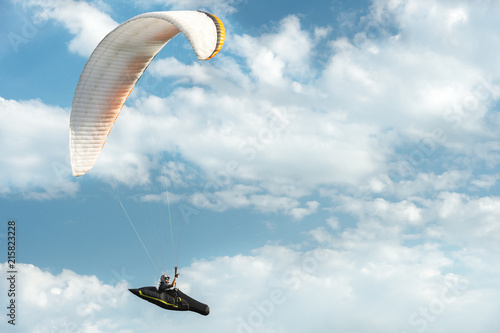 Professional paraglider flies on a white paraglider against the blue sky and white clouds. Paragliding sport © yanik88