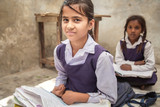 School girl in uniform of Indian Ethnicity sitting in their village classroom, looking at camera smiling.