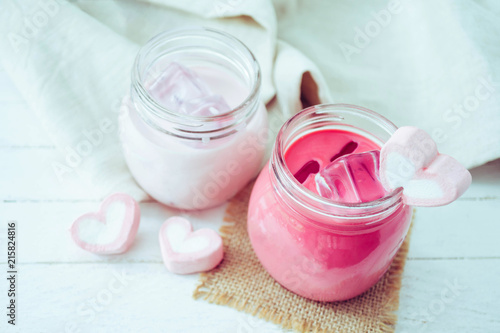 Canvas Milkshake Pink milkshake with heart shape marshmallows on wood background