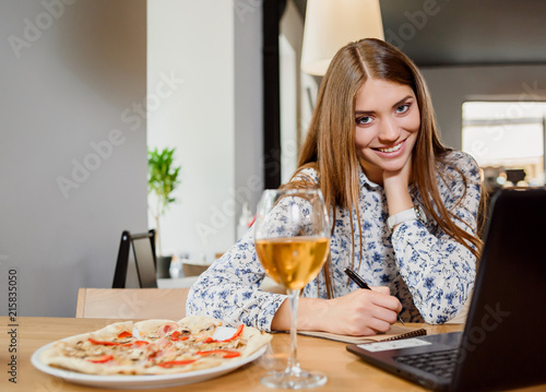 Canvas Pizzeria Gorgeous woman working with notebook in restaurant.