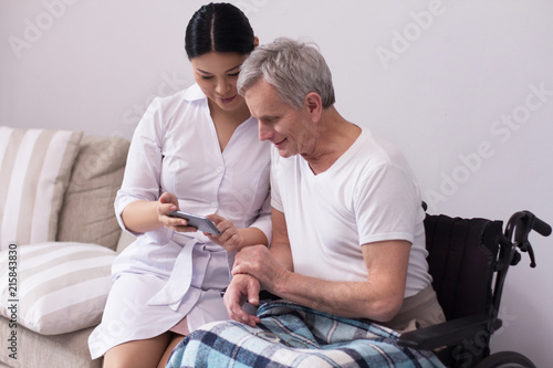 Foto Murales Female doctor sitting nxt to disabled man showing him pictures on phone. Friendly asian nurse shwoing something on her smartphone to elderly patient in wheelchair.