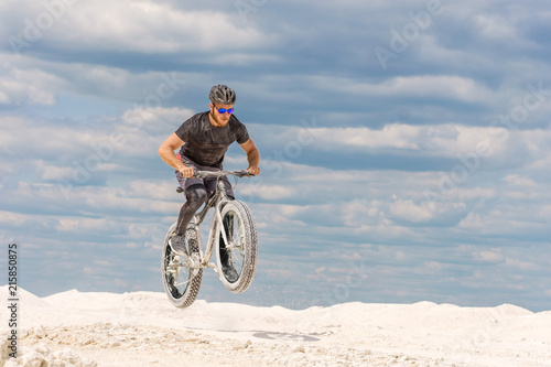 Foto Murales Training a bicyclist in a chalky quarry. A brutal man on a fat bike.