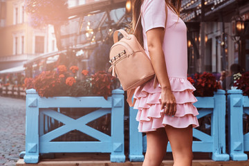 Cropped photo. Woman with long brown hair dressed in pink dress with a rucksack standing near the terrace cafe.