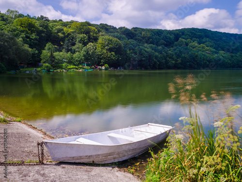 Aluminium Purper Wooden pier or jetty and a boat on lake sunset and sky reflection water.