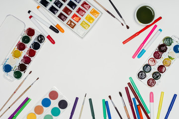 top view of arranged colorful paints, paintbrushes and markers on table