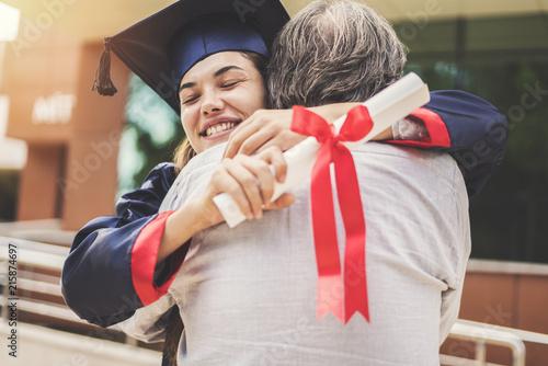Leinwandbild Motiv Graduated student hugging her father