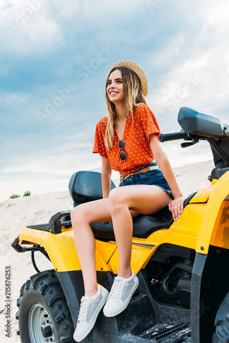 beautiful young woman sitting on all-terrain vehicle and looking away in desert