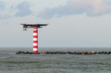 The red and white striped lighthouse with heliplatform at the entrance of the Port of Rotterdam in the Neterlands