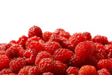 lots of ripe red raspberry berries in a bowl isolated on white background