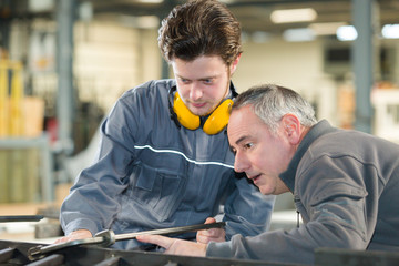 man working with apprentice in printing house