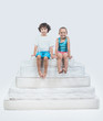 Quadro Girl and Boy Sitting on Top of Pyramid of Mattress