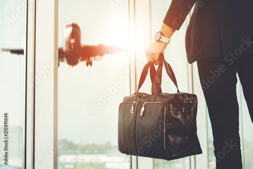 Leinwandbild Motiv Man Standing in Airport and Looking at Plane