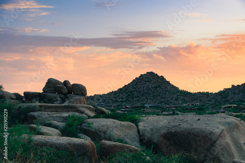 Foto Spatwand Zonsopgang Pink clouds rise over the boulders of Pinnacle Peak at dawn in Scottsdale, AZ.