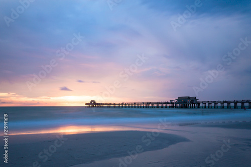 Iconic Naples Pier the symbol of this famous city in southwest Florida, USA. Amazing and calm ocean during sunset, cloudscape after a big tropical storm in the Gulf of Mexico, close to Everglades Nati