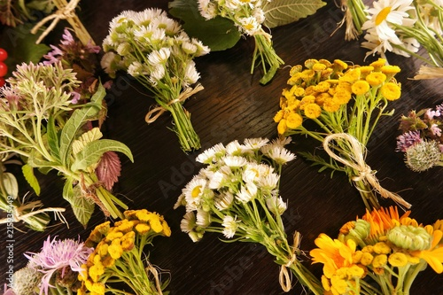 The small bouquets of wildflowers on the background of the black wooden table, floristic composition © botevvs