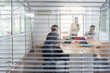Close-up of the transparent interior window of an office with three young independent workers sharing the facilities of a modern co-working space  - 215937269