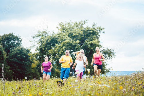 Foto Spatwand Hardlopen Family running on a meadow with flowers for sport