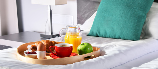 Breakfast on tray in bed in hotel room © monticellllo